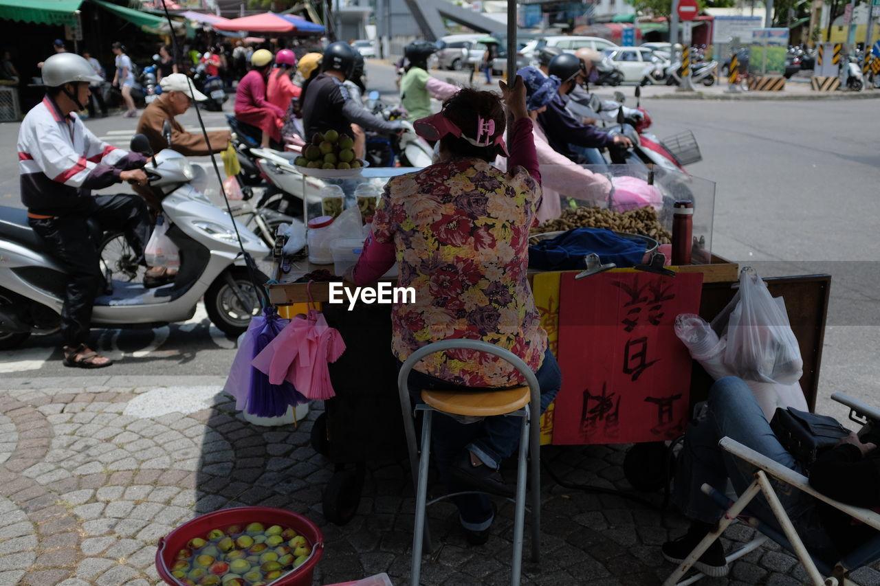 PEOPLE SITTING ON STREET MARKET