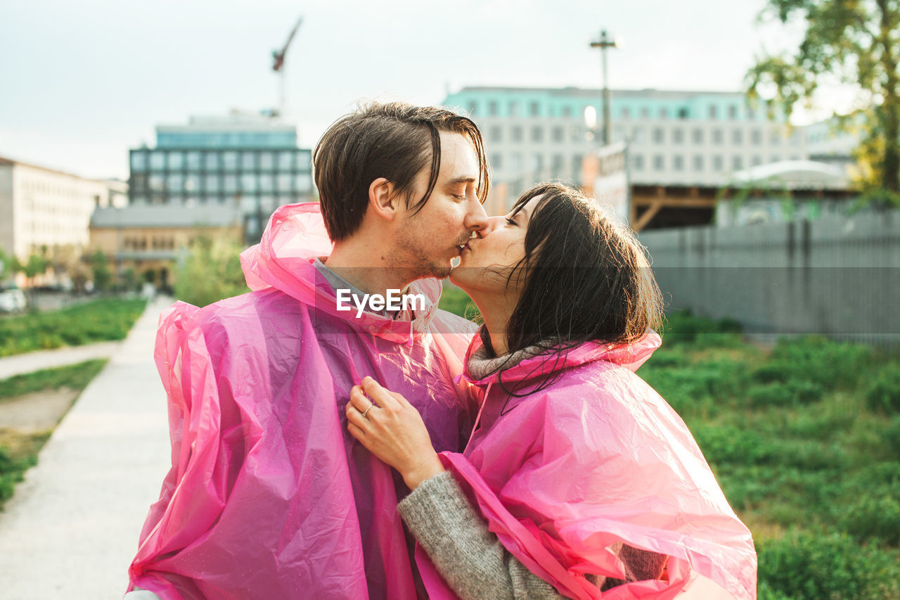 Young Couple Wearing Pink Raincoat While Kissing In City