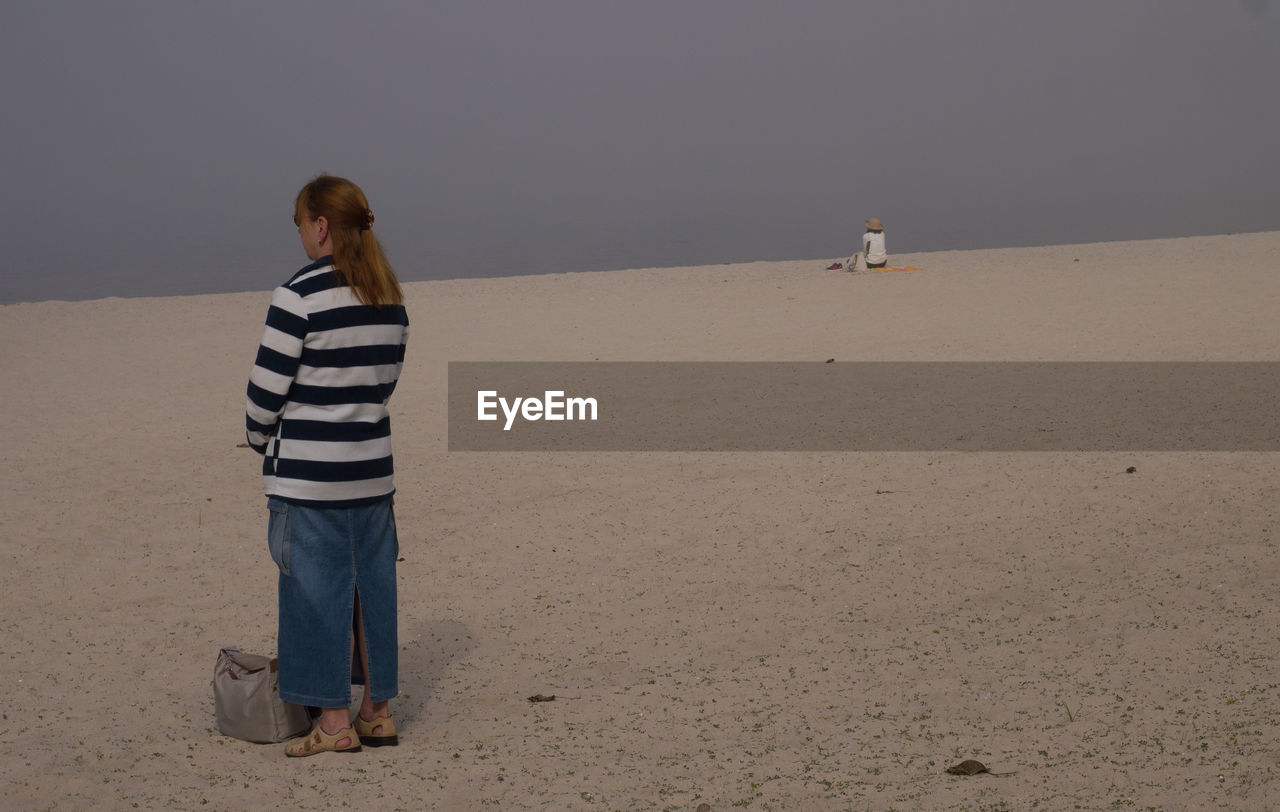 Rear View Of Woman Standing On Sand At Beach