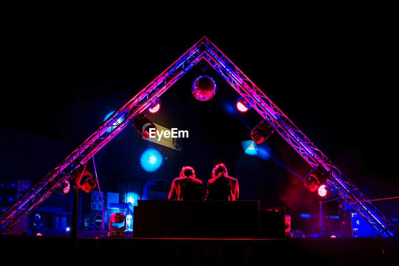 night, illuminated, group of people, arts culture and entertainment, real people, men, enjoyment, performance, event, lifestyles, low angle view, people, architecture, group, lighting equipment, music, leisure activity, medium group of people, light - natural phenomenon, nightlife, stage, festival