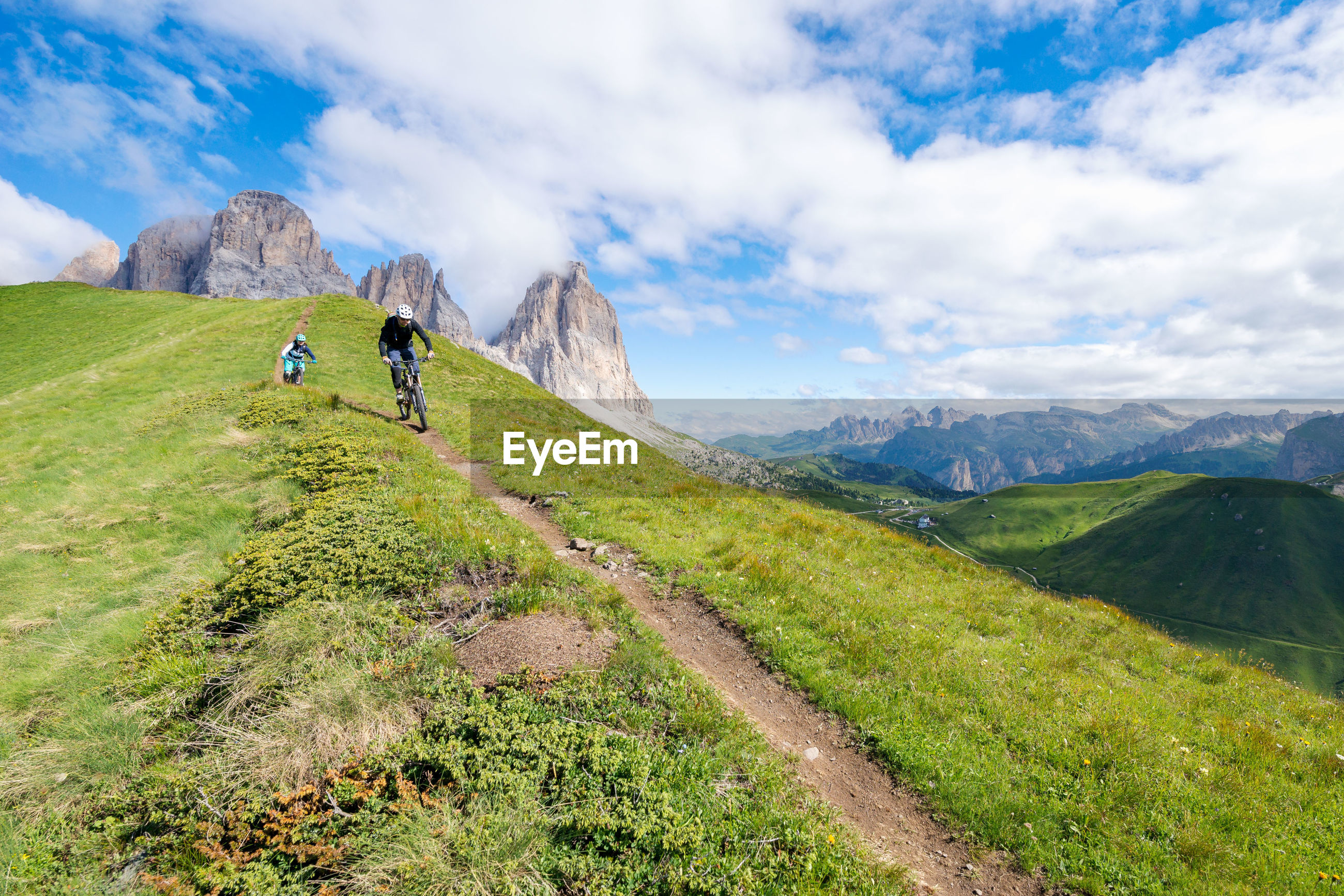 Low angle view of people riding bicycles on mountain