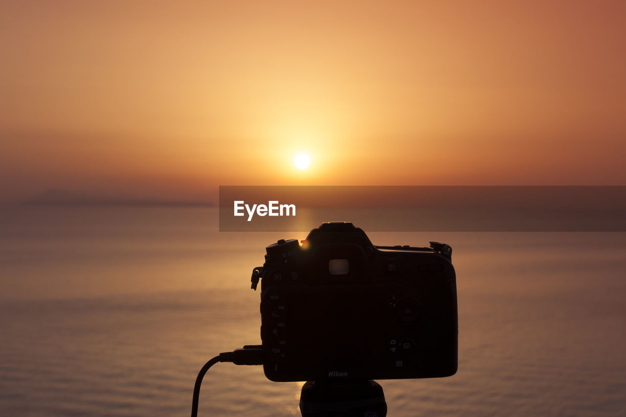 Close-up of camera against sky during sunset