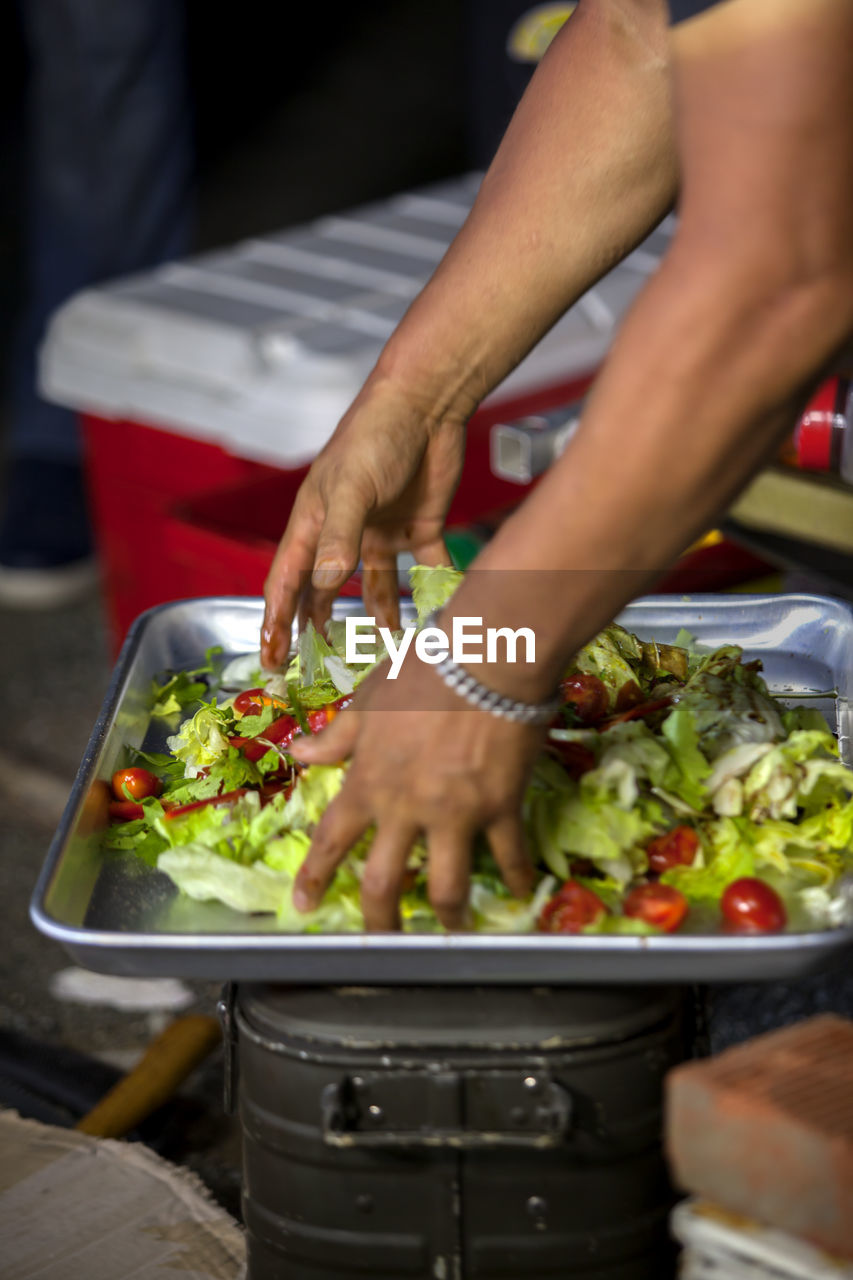 Man Tossing Salad In Tray