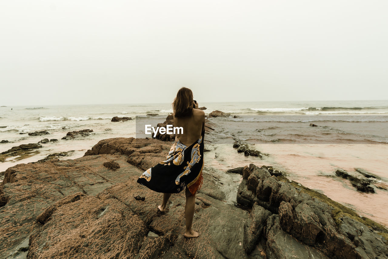 Rear view of woman standing on rock at beach against clear sky