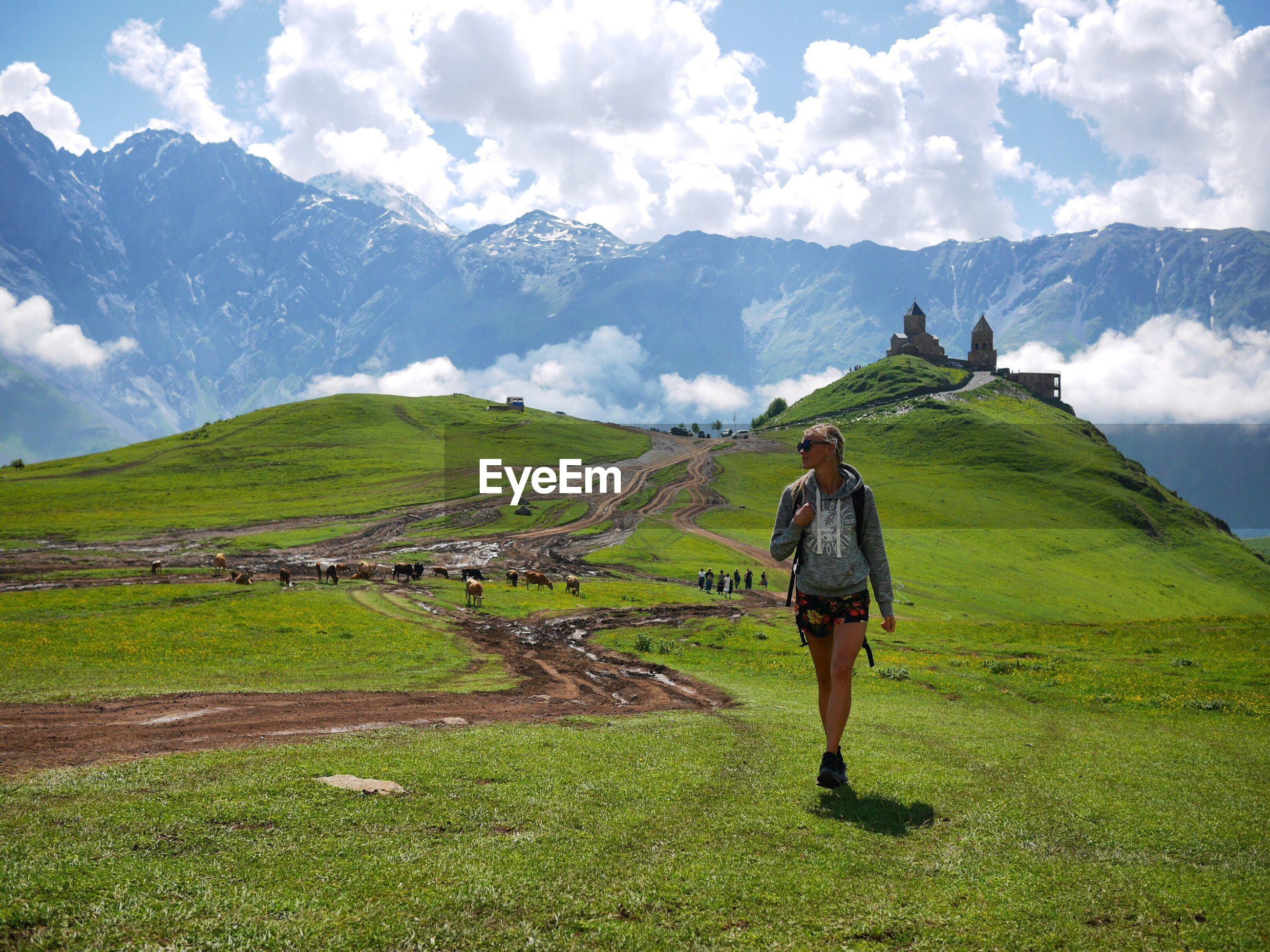 Woman walking on grassy field against sky