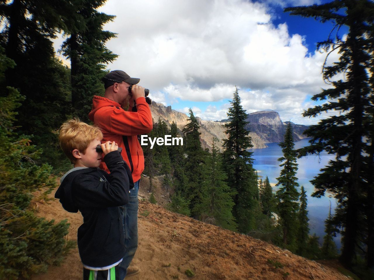 Father And Son Looking Through Binoculars At Crater Lake