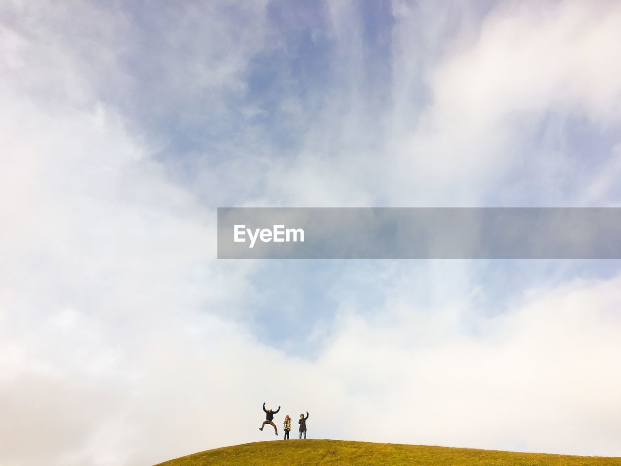 Three people on mountain against cloudy sky