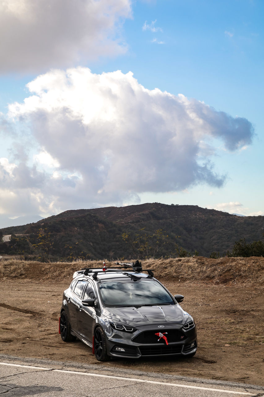 transportation, motor vehicle, car, mode of transportation, sky, cloud - sky, land vehicle, mountain, environment, nature, day, landscape, no people, scenics - nature, non-urban scene, travel, beauty in nature, stationary, outdoors, road, sports utility vehicle