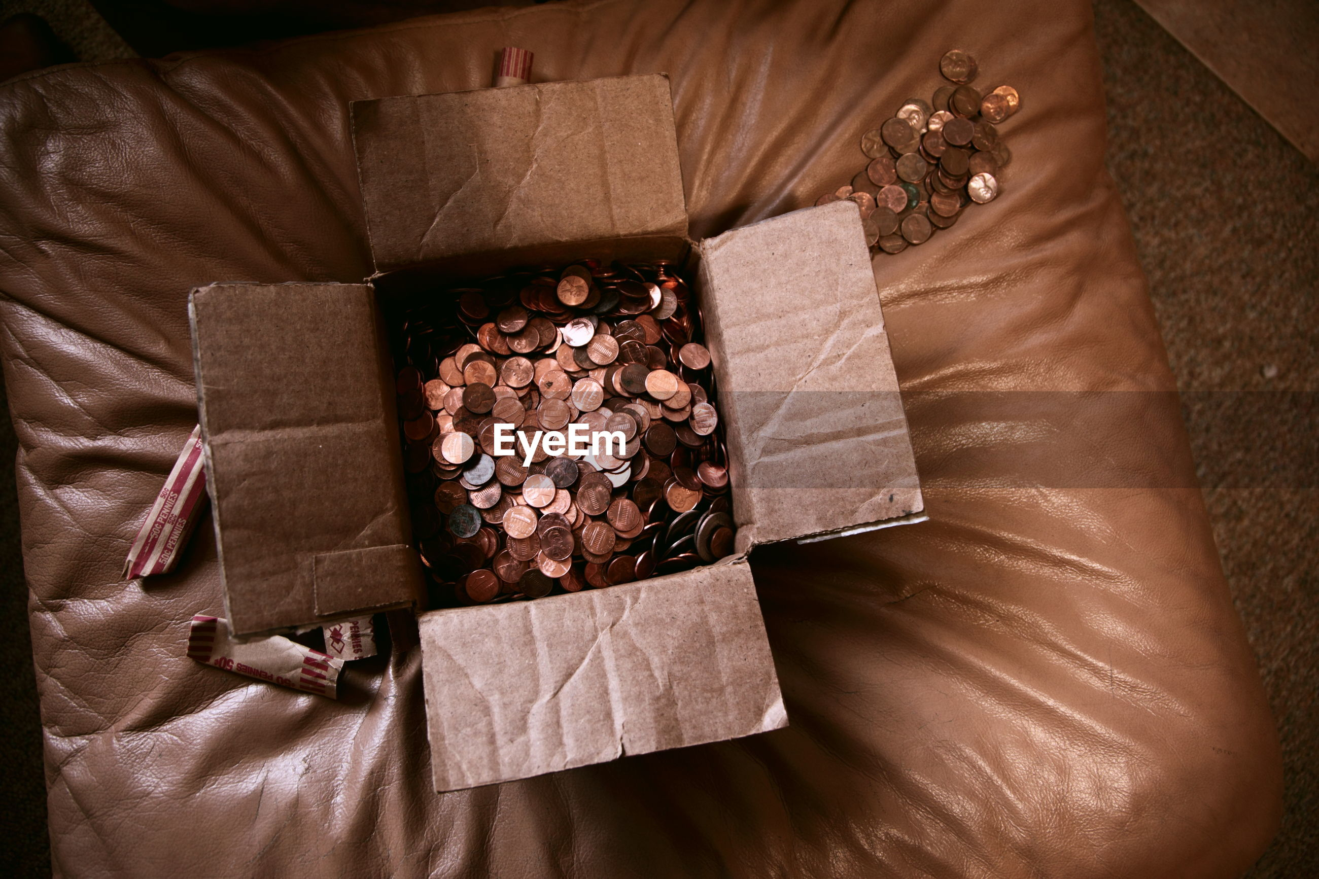 High angle view of us coins in box on ottoman at home