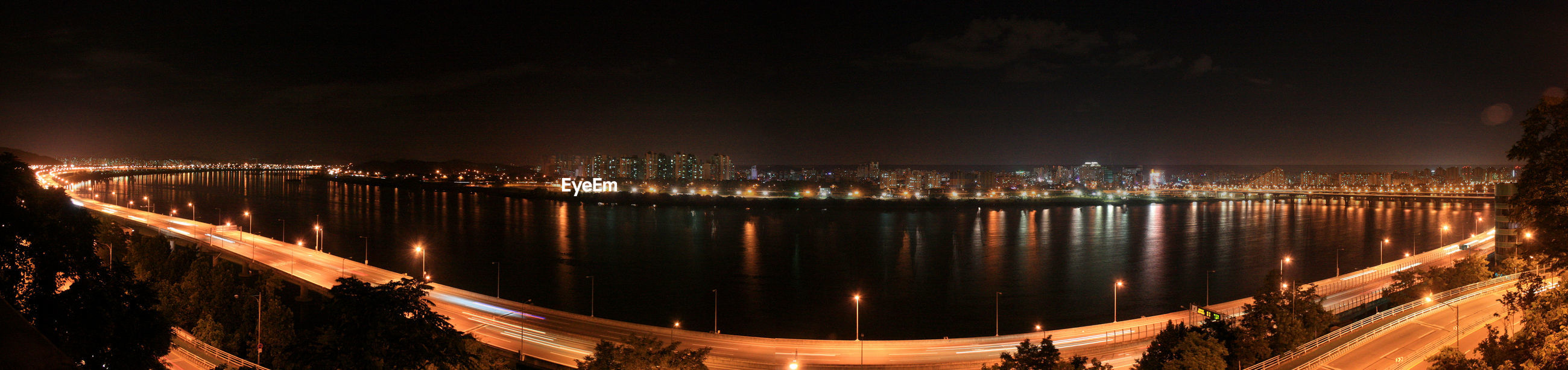 Panoramic view of river against sky in illuminated city at night