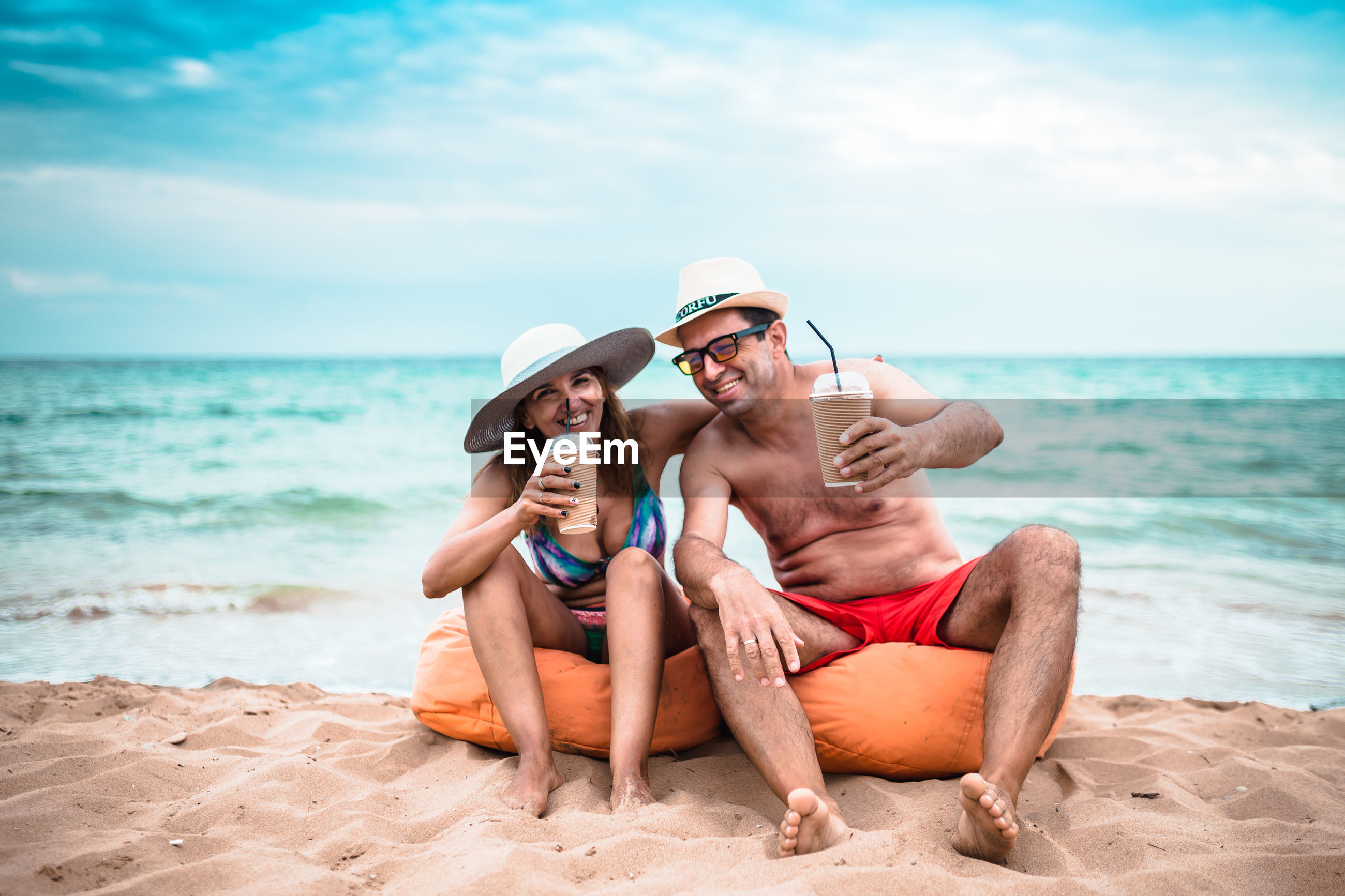 Mature couple having drinks while sitting at beach