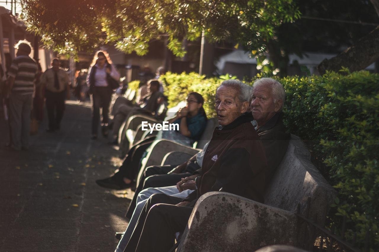 PEOPLE SITTING ON SIDEWALK