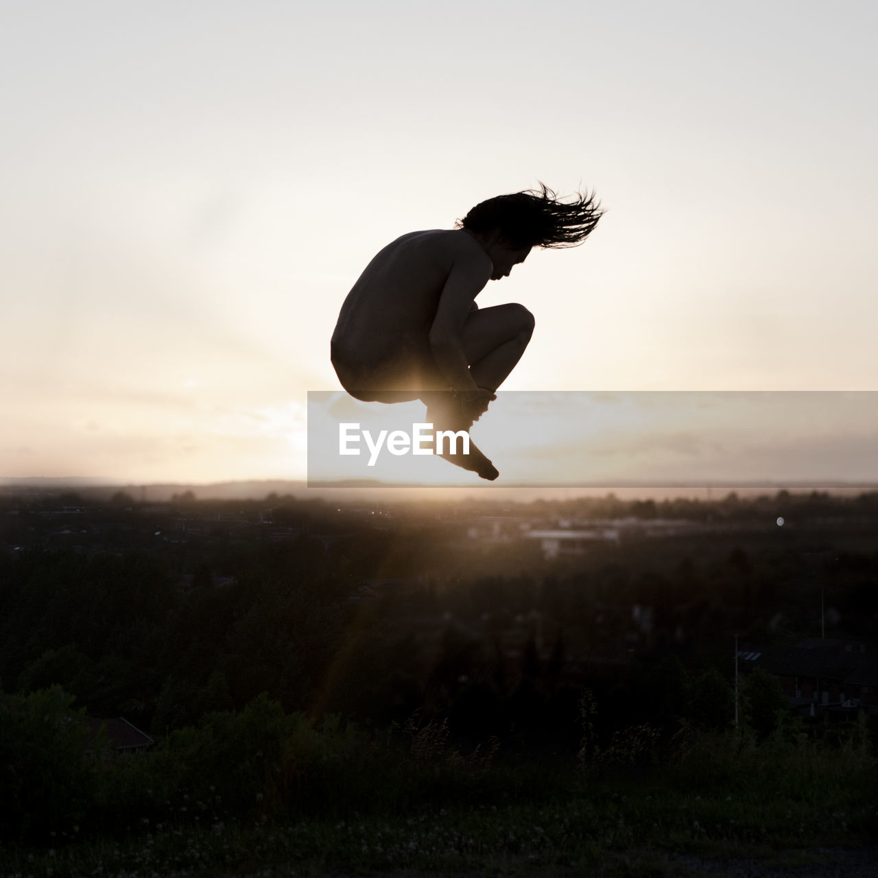 Silhouette Of Man Jumping At Sunset