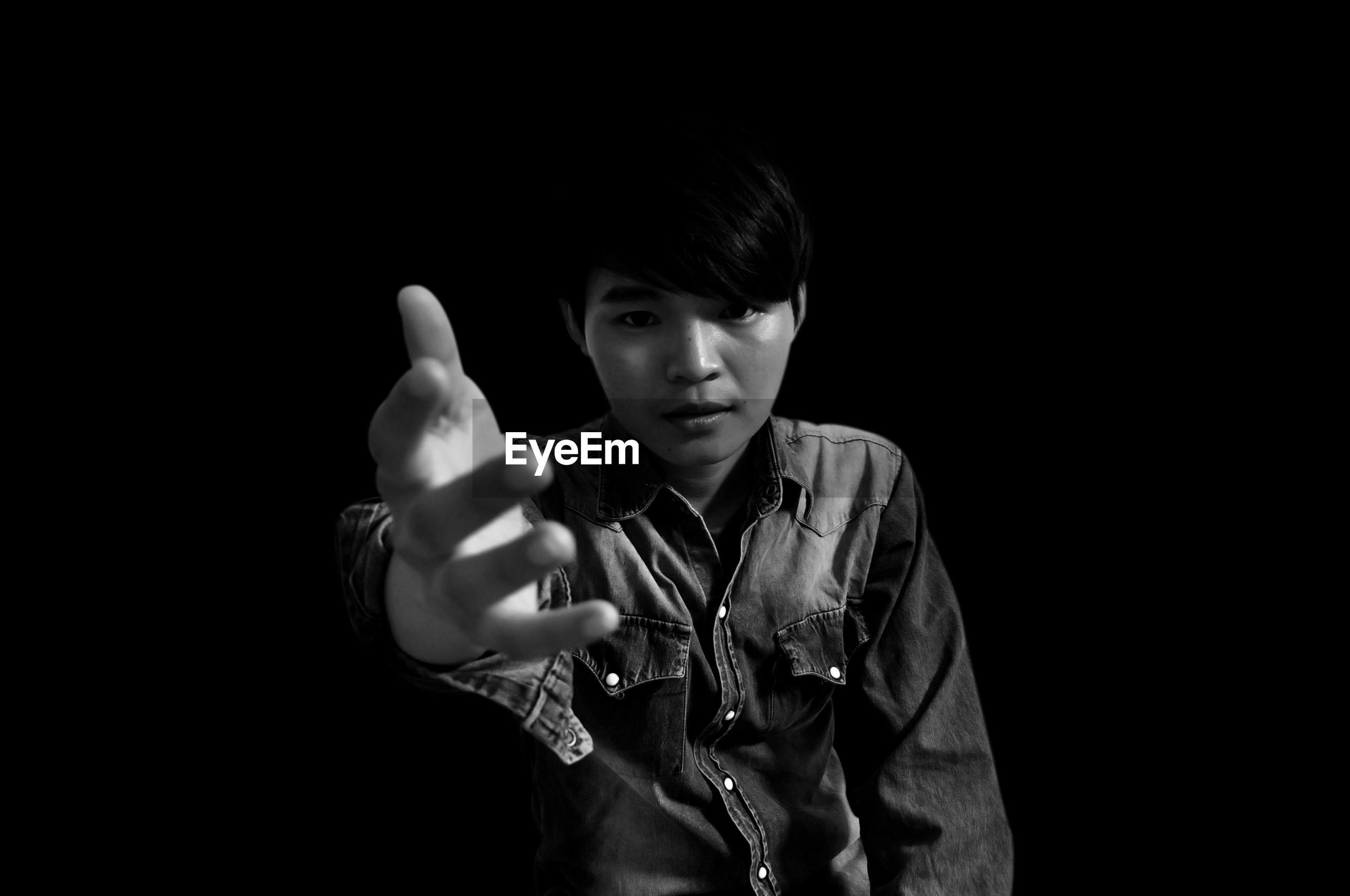 Portrait of man gesturing against black background