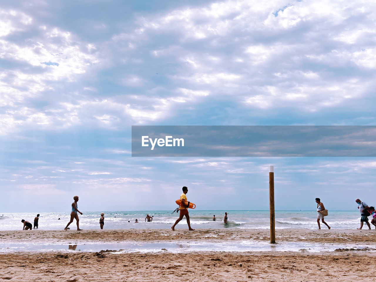PEOPLE PLAYING ON BEACH AGAINST SEA
