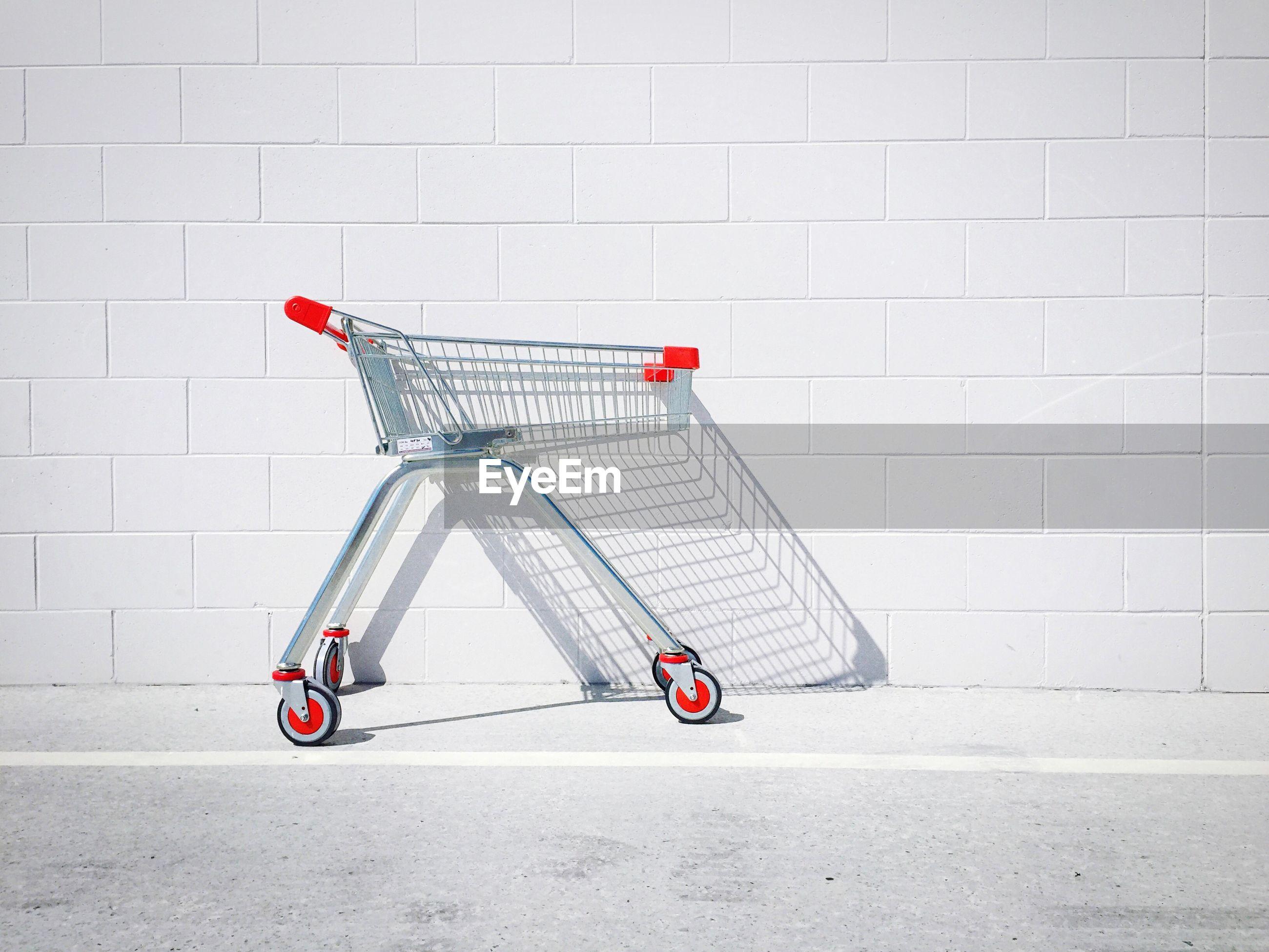 Shopping cart against white wall