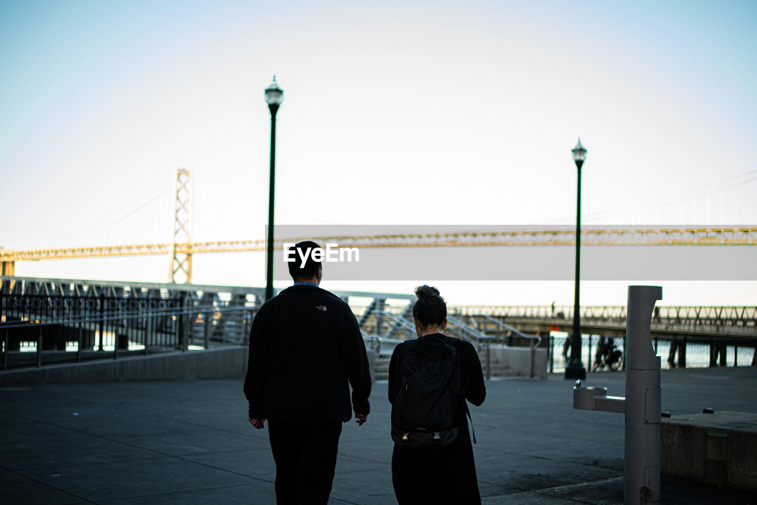 REAR VIEW OF FRIENDS STANDING ON BRIDGE AGAINST SKY