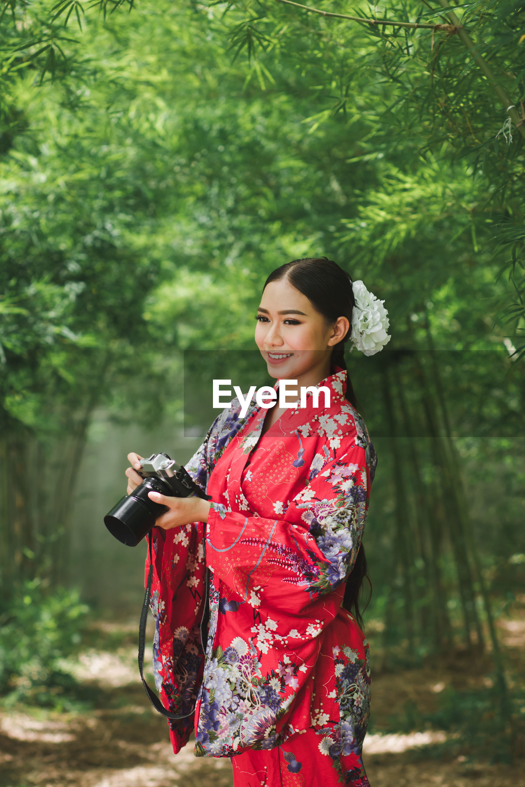 Smiling young woman wearing kimono holding digital camera in forest