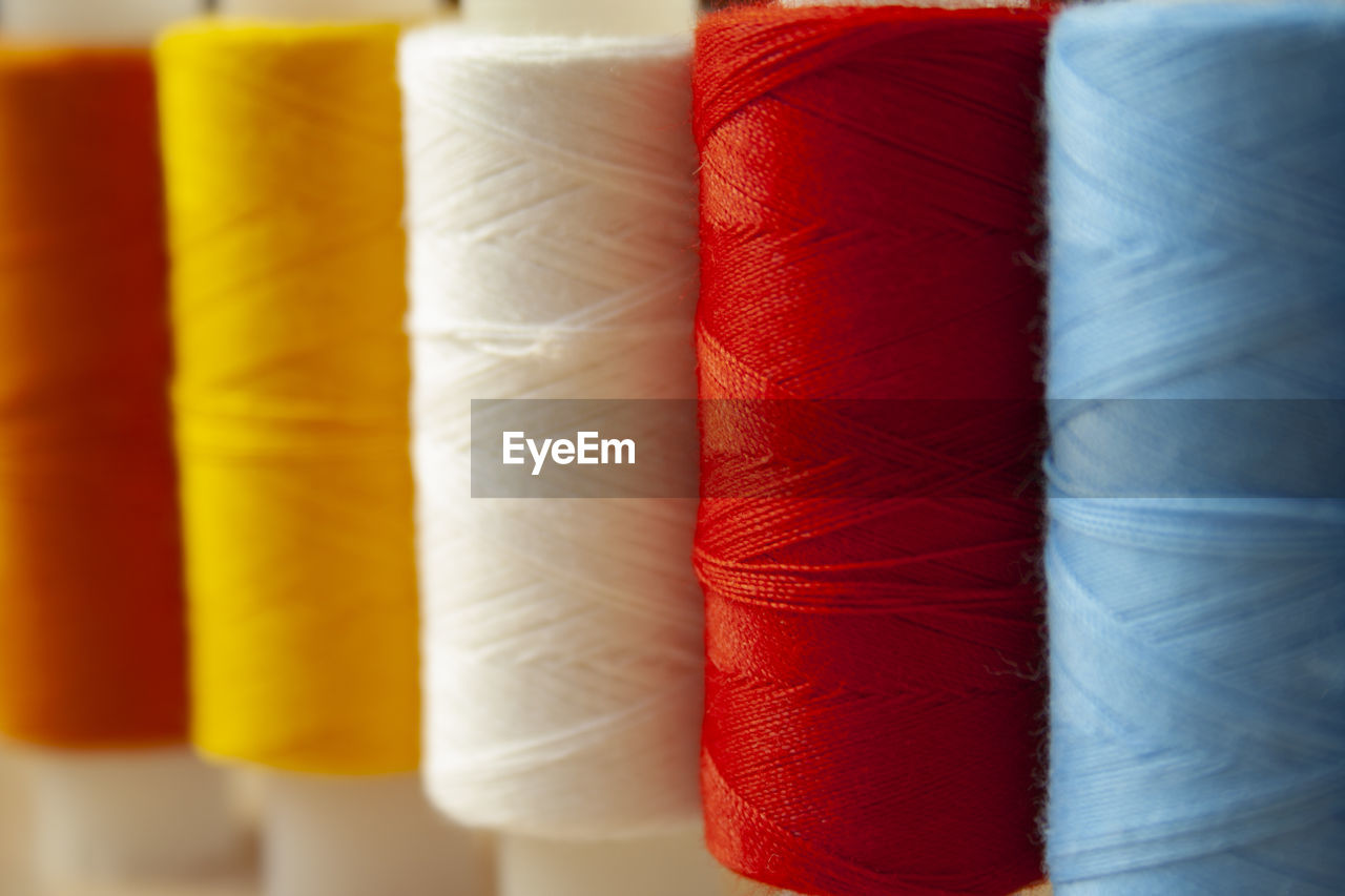 red, multi colored, close-up, no people, choice, still life, spool, full frame, thread, indoors, variation, textile, backgrounds, in a row, selective focus, side by side, rolled up, industry, pattern, yellow, softness