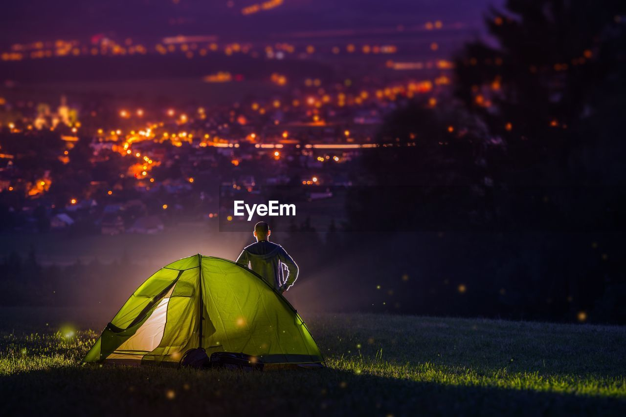 Rear view of man standing by tent at night