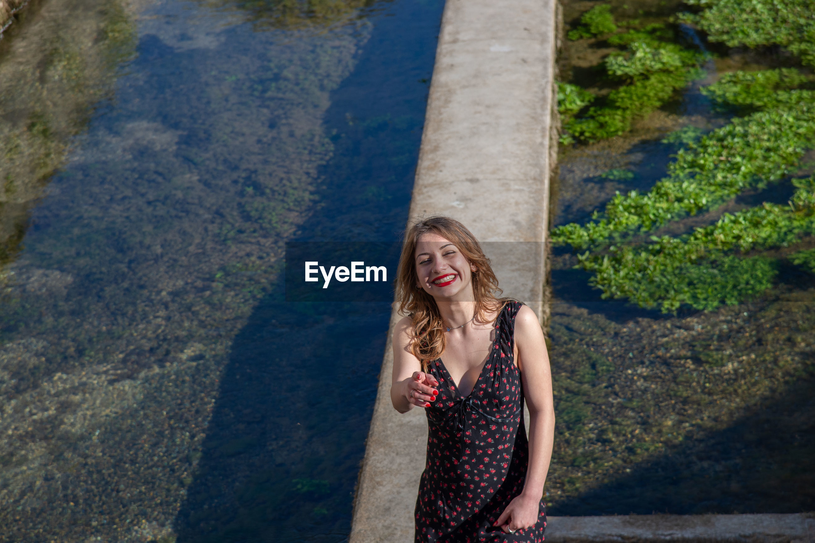 Smiling young woman pointing while standing by canal on retaining wall