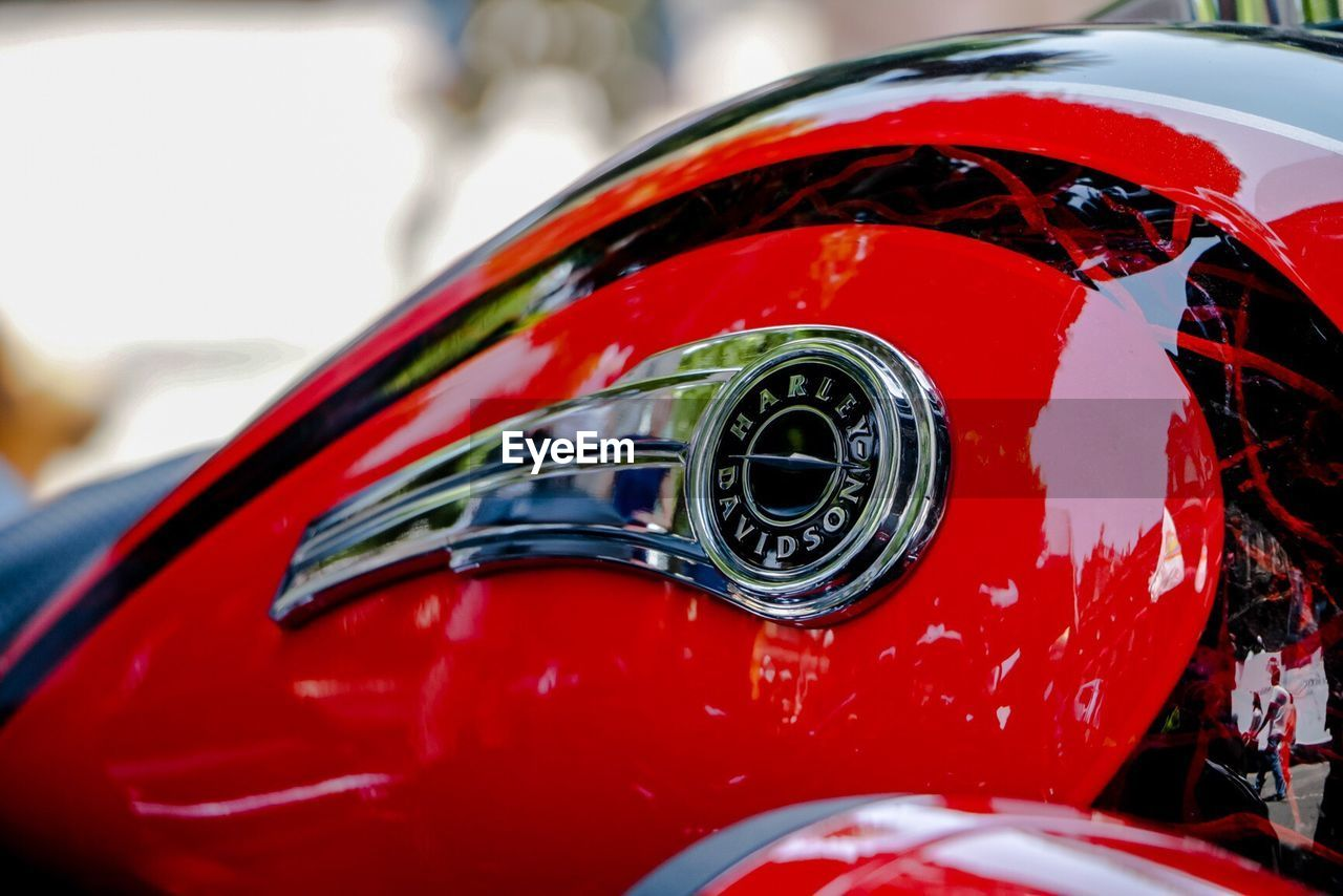 CLOSE UP OF RED CAR ON SIDE-VIEW MIRROR