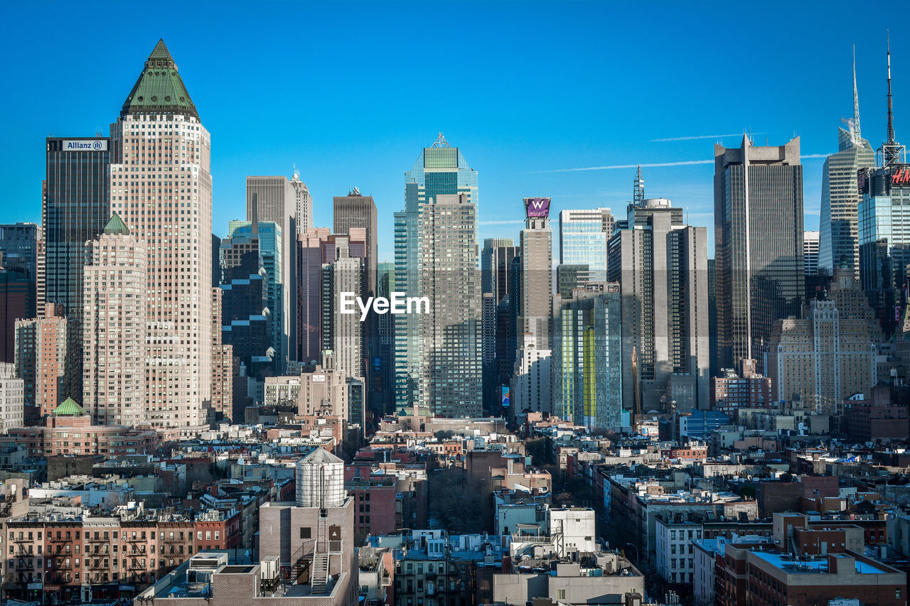 building exterior, building, architecture, built structure, office building exterior, city, skyscraper, cityscape, sky, tall - high, tower, modern, urban skyline, residential district, travel destinations, office, landscape, crowd, clear sky, financial district, outdoors, spire