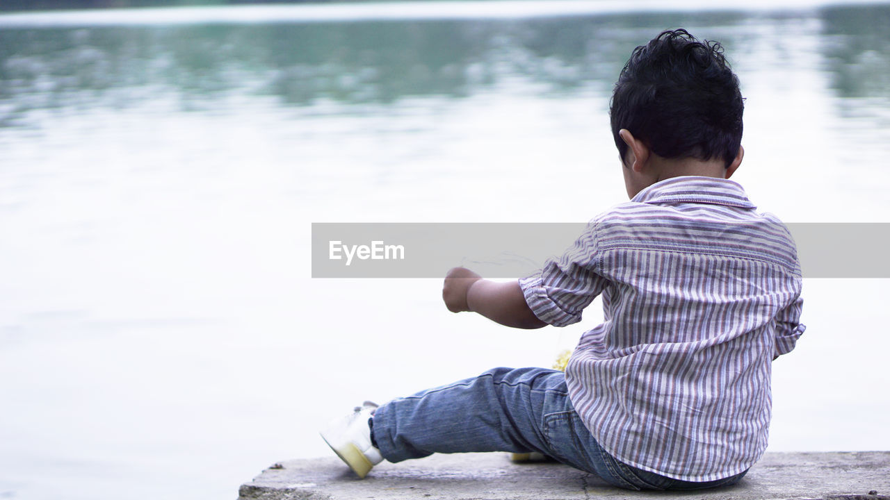 water, one person, real people, rear view, leisure activity, lifestyles, casual clothing, men, lake, sitting, focus on foreground, relaxation, day, nature, full length, child, childhood, males, outdoors, looking at view