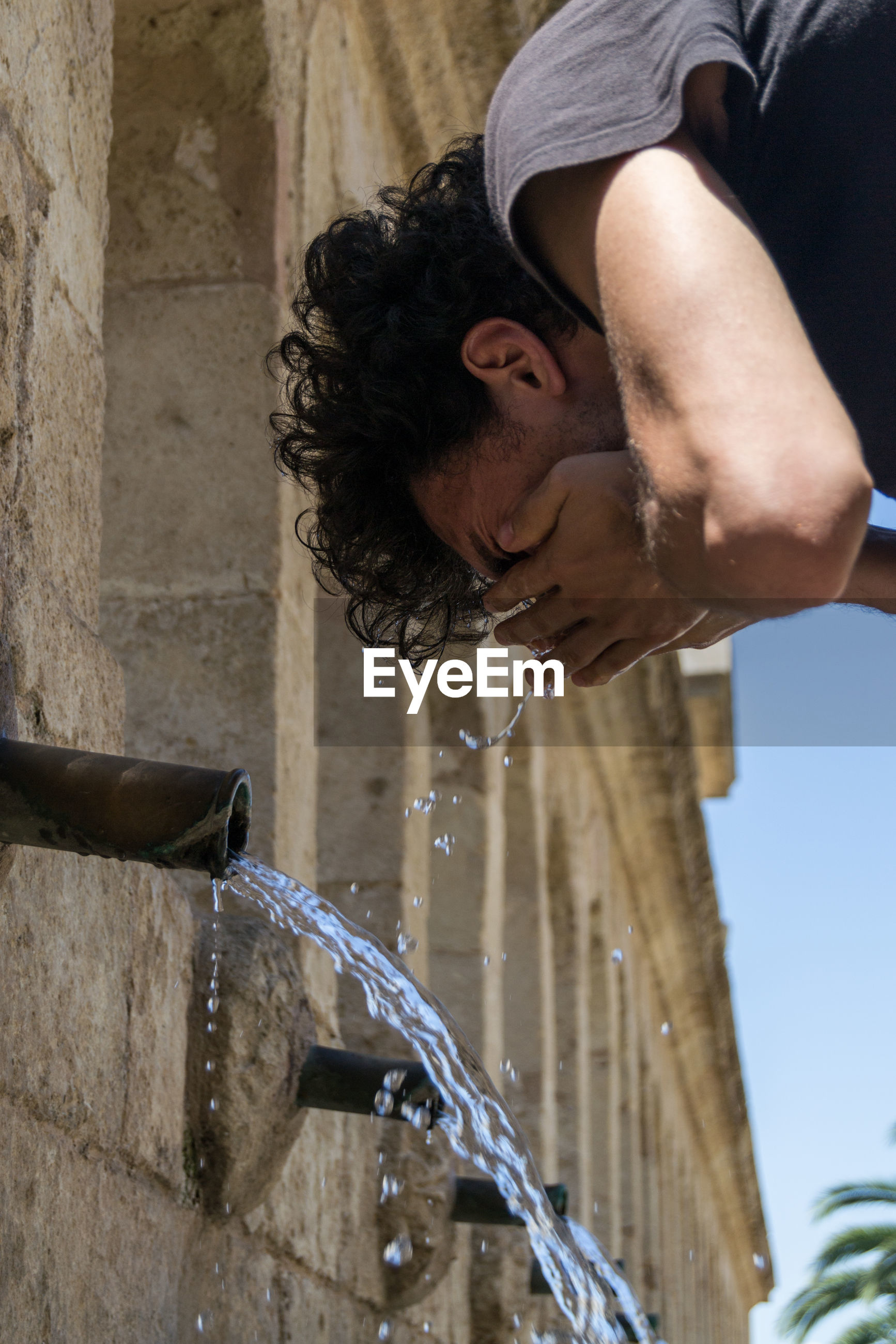 Low angle view of man washing face at drinking fountain