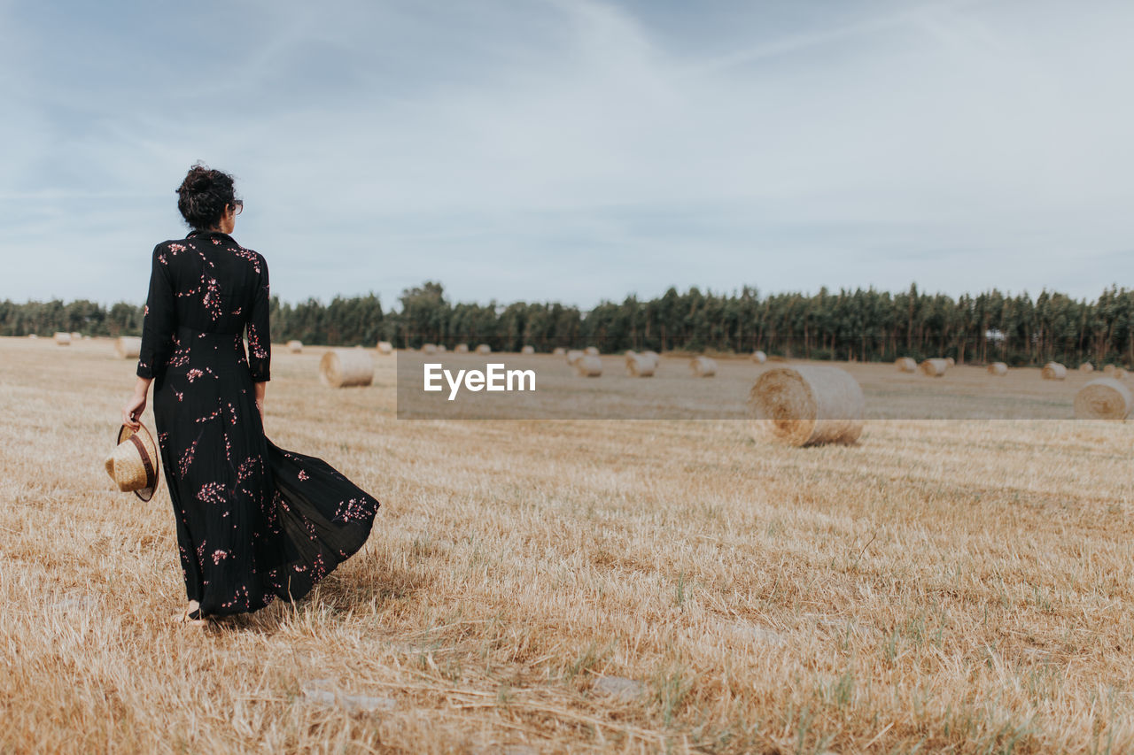 Rear View Of Woman By Hay Bales On Field