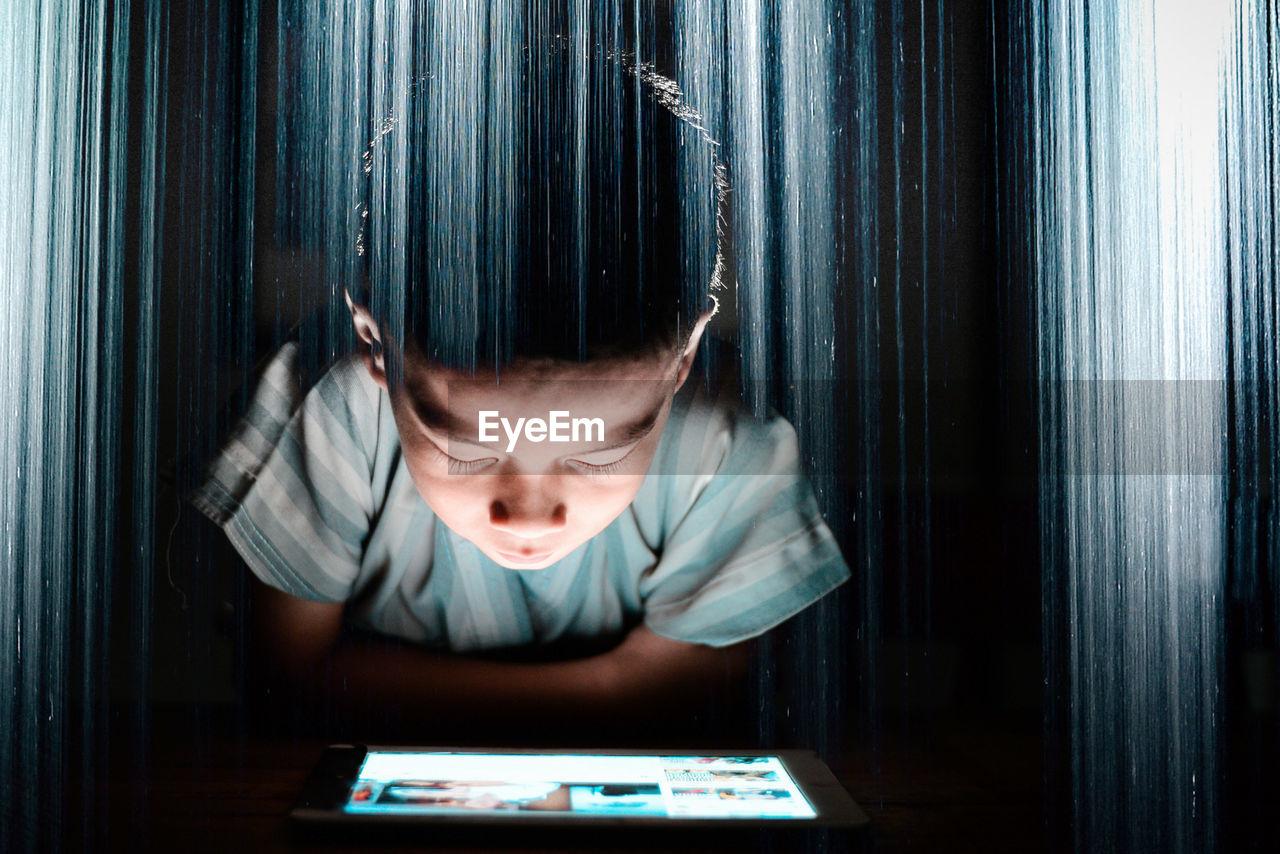 Close-Up Of Boy Looking In Digital Tablet