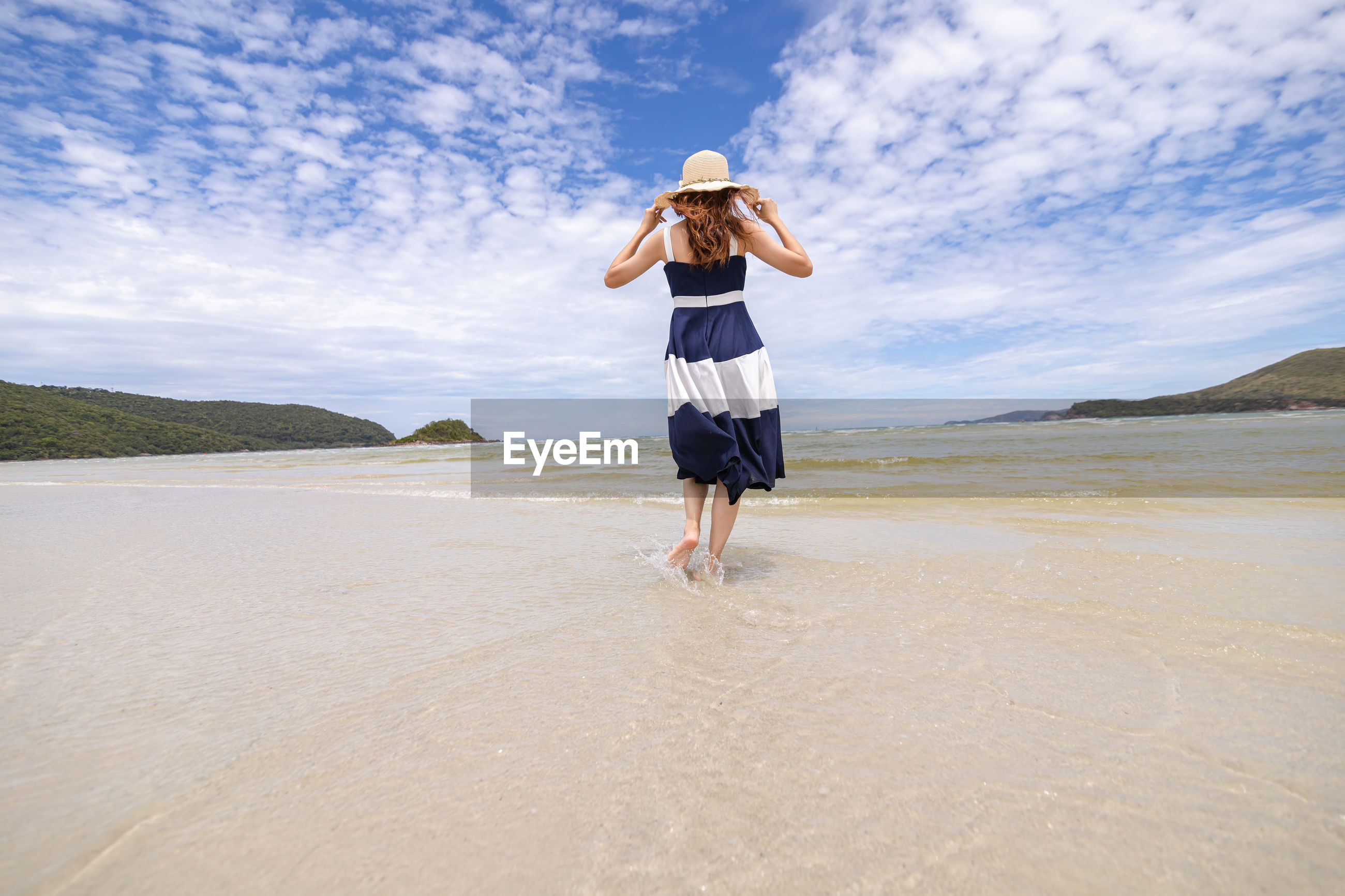 Full length rear view of woman standing at beach