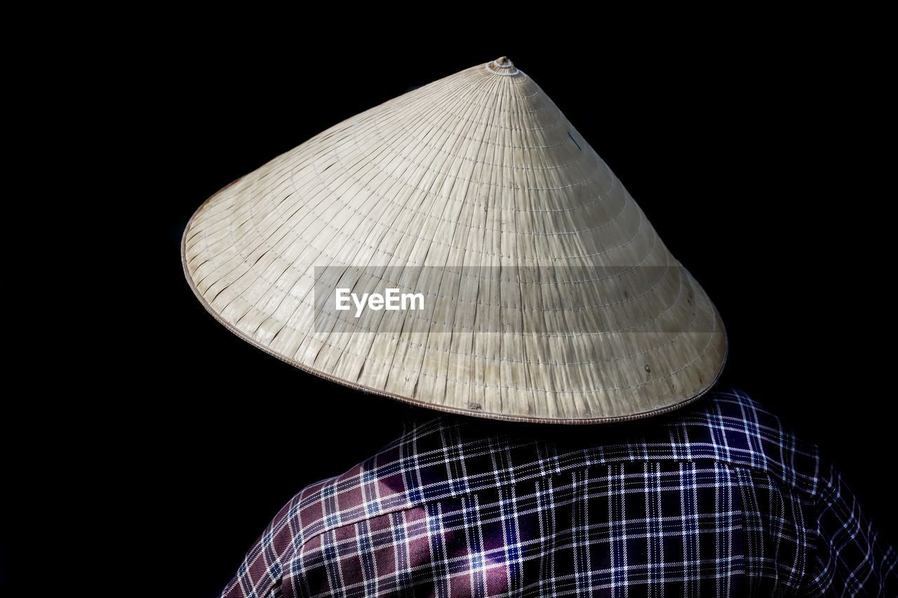 Rear View Of Man Wearing Asian Style Conical Hat Against Black Background