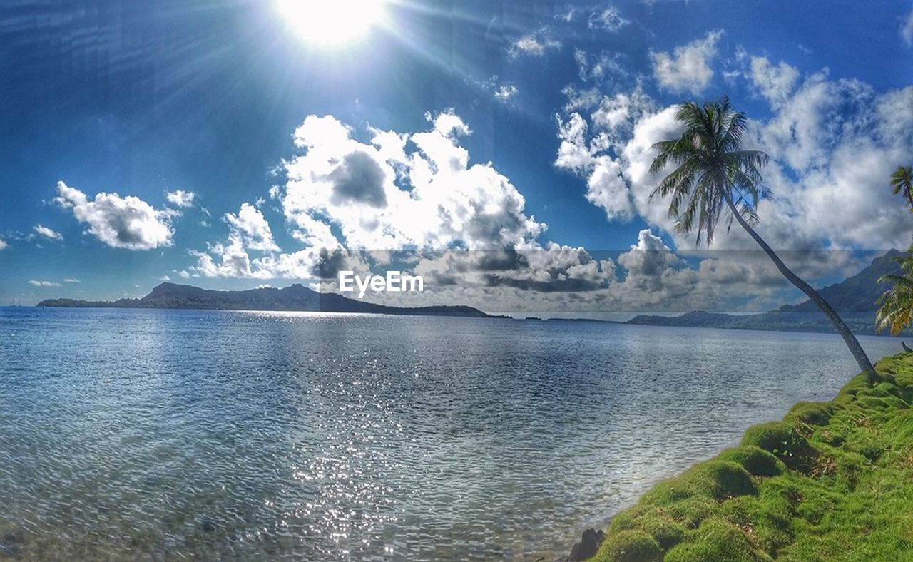 sky, water, cloud - sky, scenics - nature, beauty in nature, tranquil scene, tranquility, sunlight, day, nature, non-urban scene, plant, no people, sunbeam, tree, mountain, sunny, idyllic, sea, sun, outdoors, lens flare