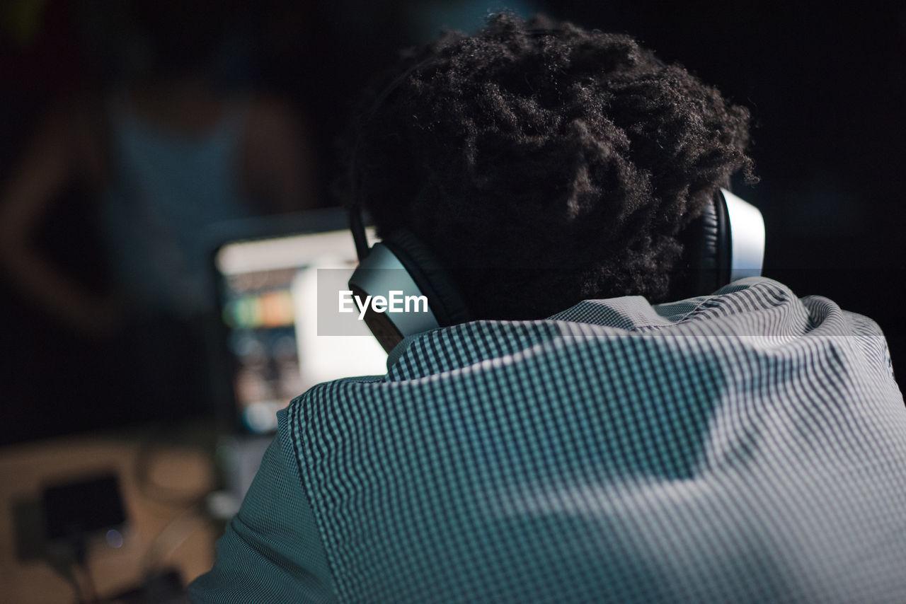 Rear View Of Dj Using Headphones
