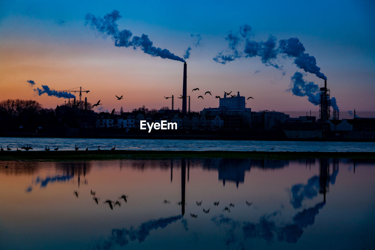 reflection, industry, sky, smoke stack, architecture, built structure, emitting, smoke - physical structure, factory, water, pollution, silhouette, building exterior, waterfront, no people, sunset, cloud - sky, chimney, fumes, outdoors, power station, nature, windmill, day