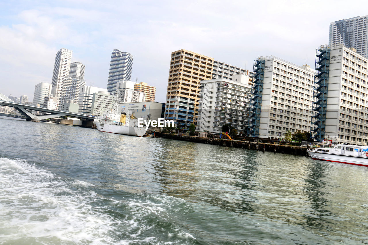 architecture, building exterior, skyscraper, city, built structure, waterfront, water, river, nautical vessel, day, cityscape, transportation, outdoors, modern, urban skyline, no people, sky, nature