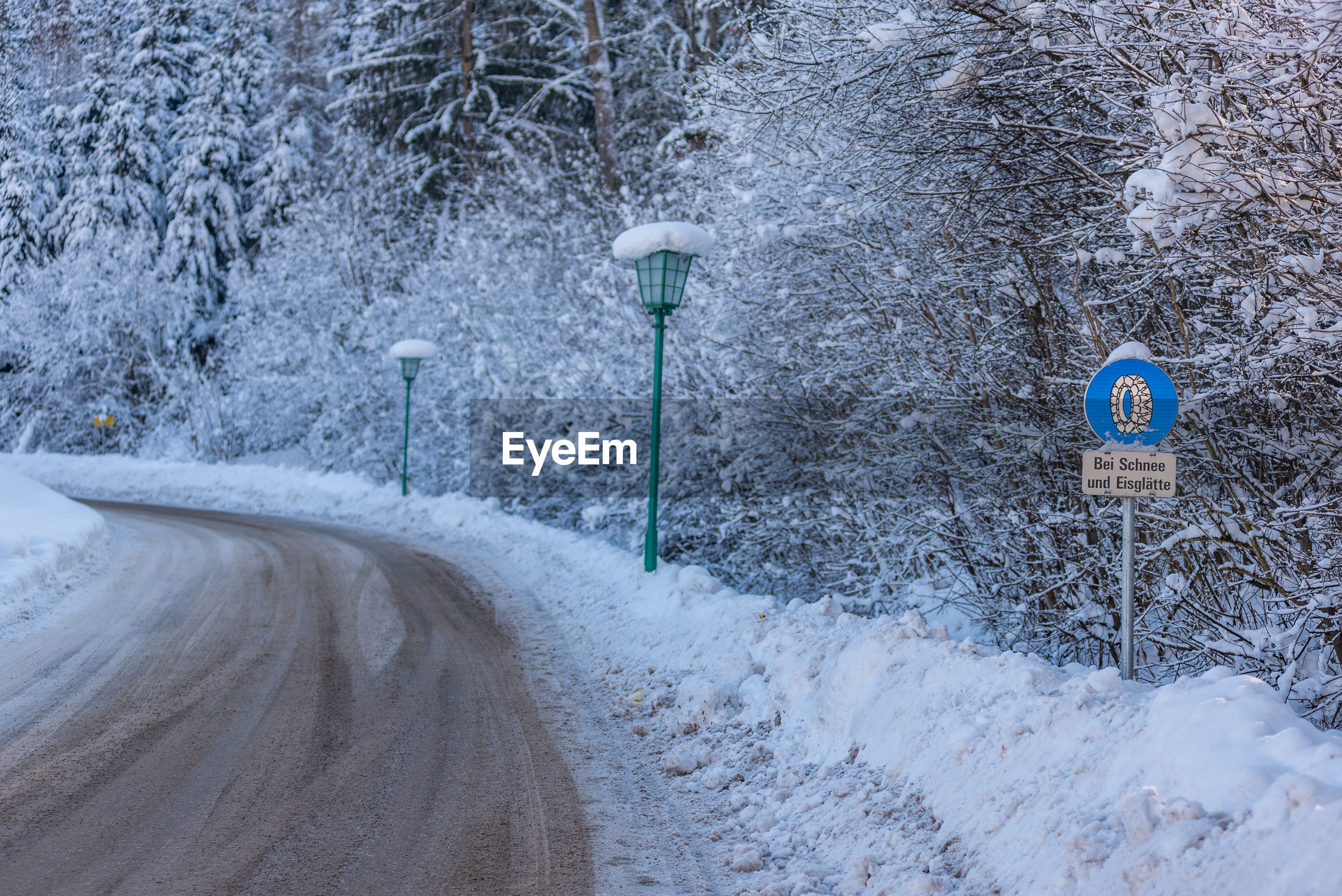 Snow covered road, green street lamps and trees. warning traffic sign. chains recorded.