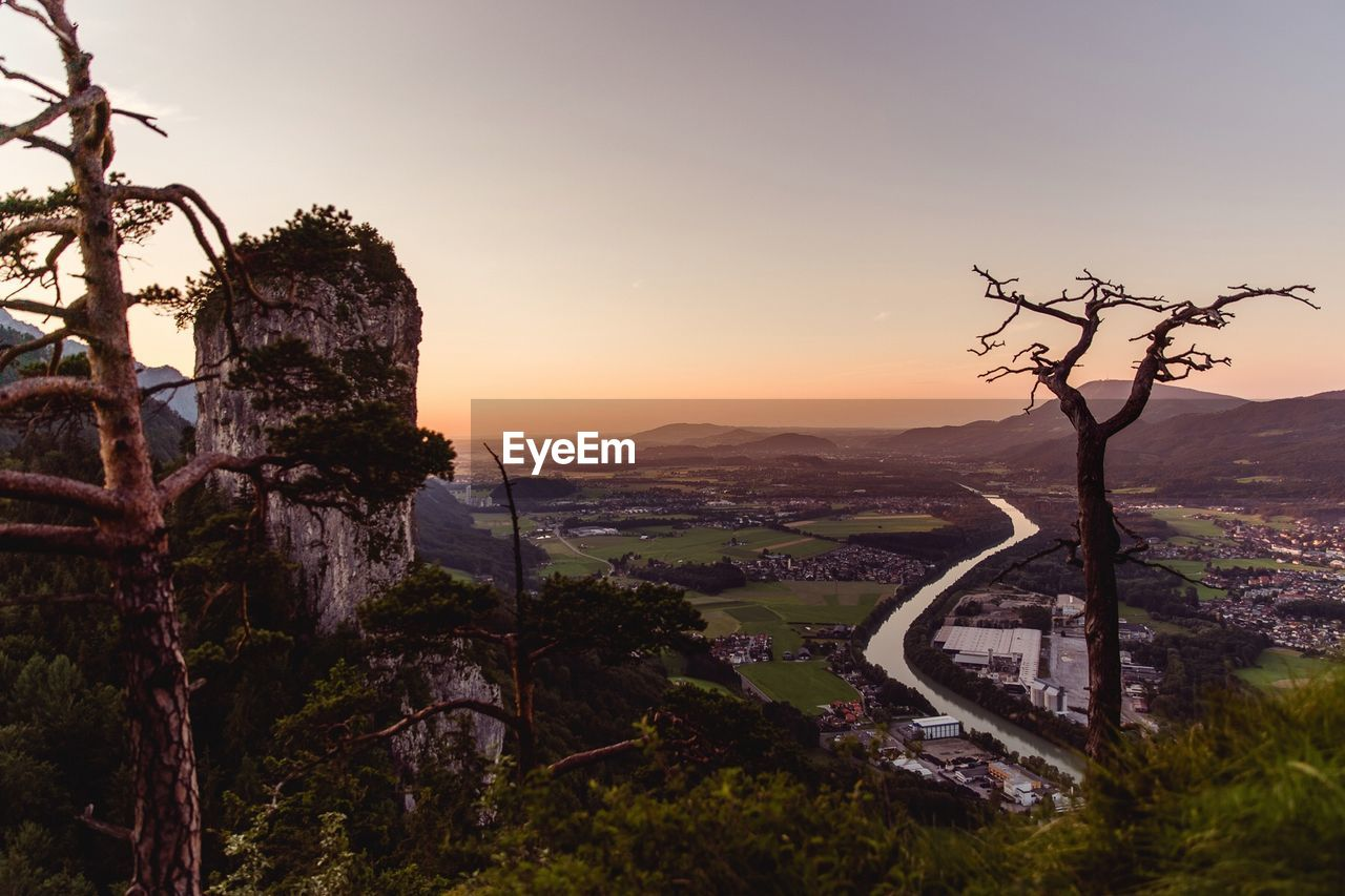 Scenic view of river on landscape against clear sky at sunset
