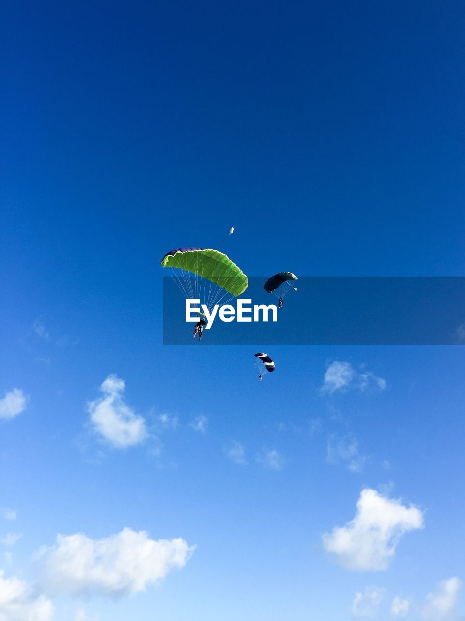 adventure, extreme sports, sky, flying, unrecognizable person, low angle view, sport, parachute, paragliding, mid-air, real people, leisure activity, blue, day, cloud - sky, lifestyles, nature, joy, two people, freedom, outdoors, skydiving, parasailing