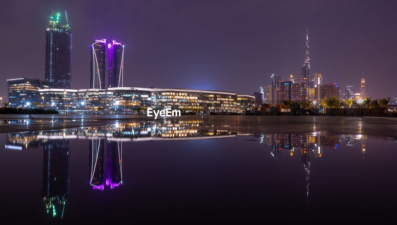 building exterior, architecture, built structure, illuminated, night, reflection, city, office building exterior, building, water, skyscraper, waterfront, no people, nature, travel destinations, urban skyline, tower, sky, cityscape, tall - high, modern, outdoors, financial district, purple, luxury, spire, nightlife