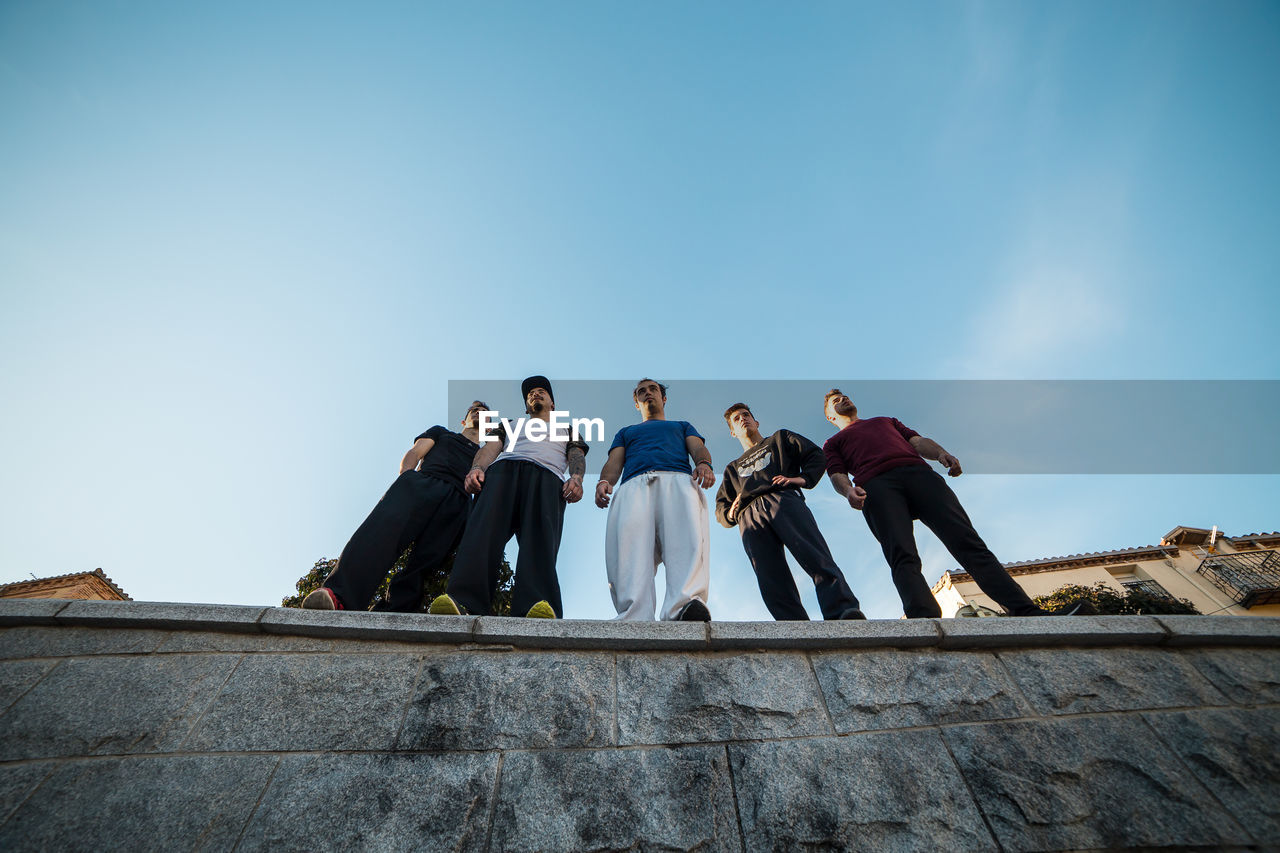 Low Angle View Of Male Friends Standing On Retaining Wall Against Sky