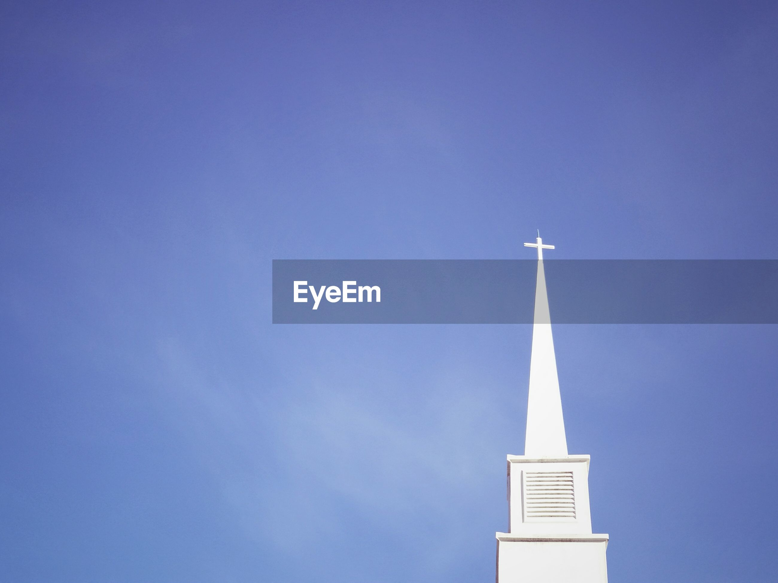 Low angle view of built structure steeple against blue sky