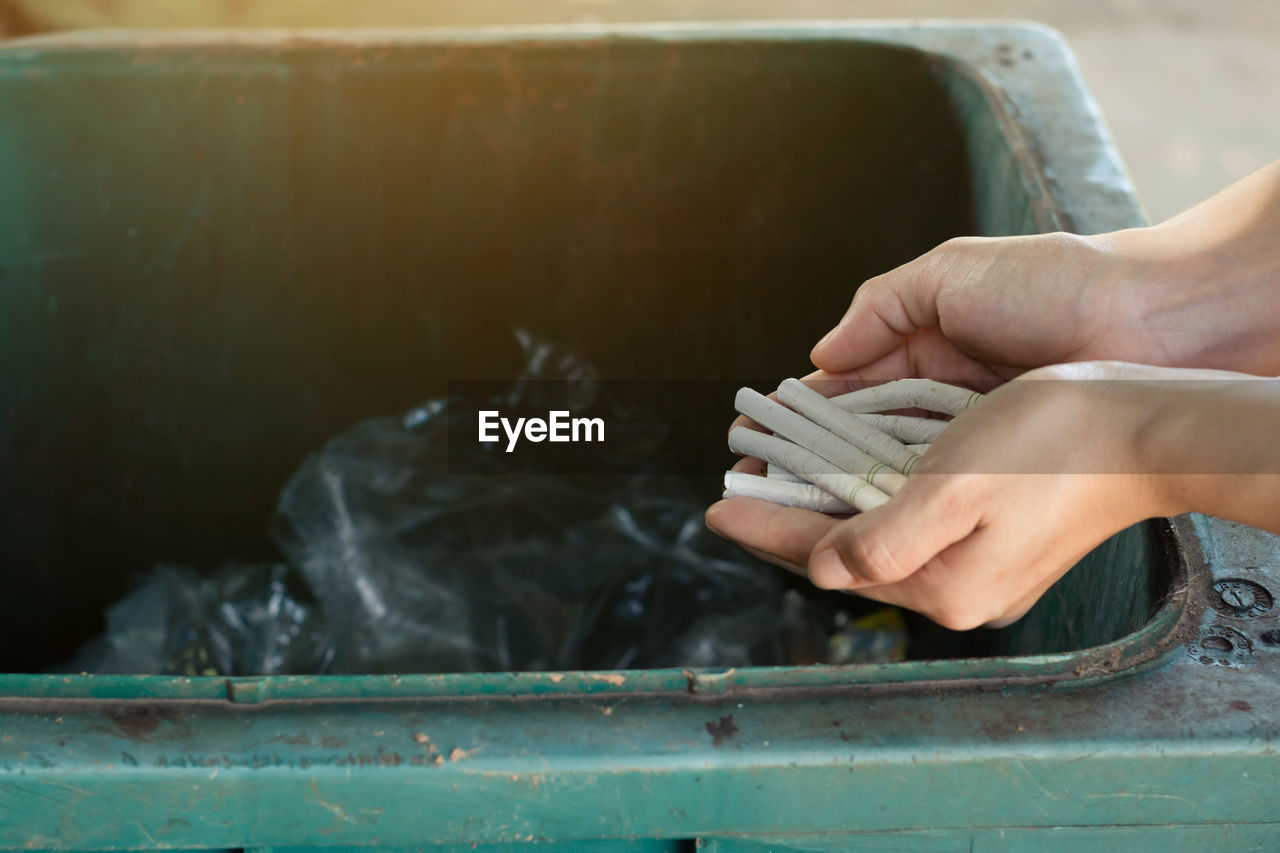 Close-Up Of Hand Holding Cigarettes Over Garbage Bin