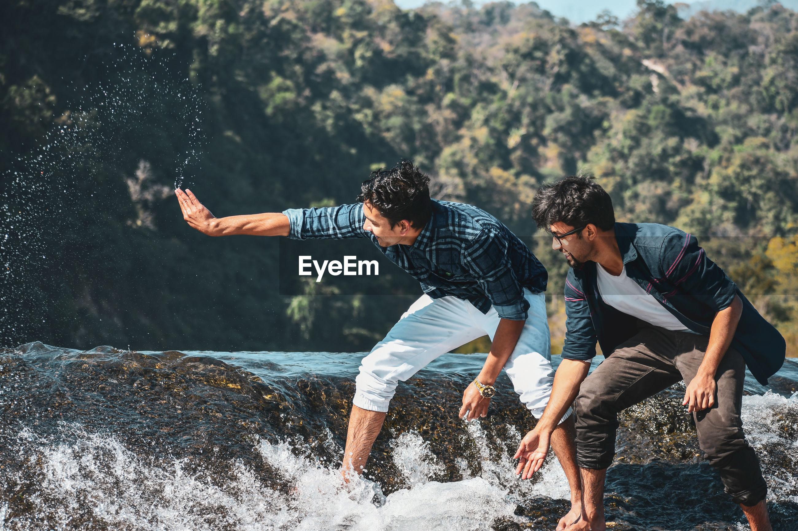 MEN PLAYING WITH WATER SPLASHING