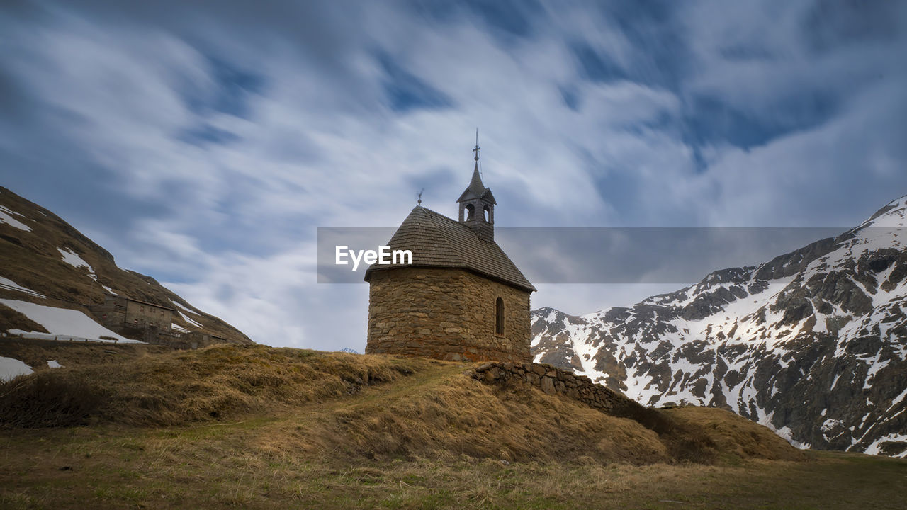 sky, cloud - sky, architecture, built structure, mountain, building exterior, nature, building, low angle view, tower, environment, beauty in nature, scenics - nature, history, cold temperature, religion, place of worship, the past, no people, outdoors, snowcapped mountain