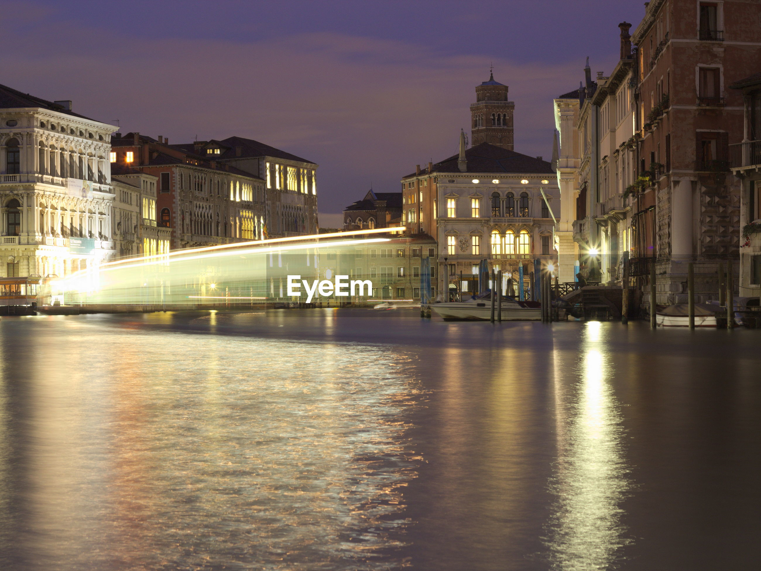 Light trail on river by illuminated buildings against sky at night
