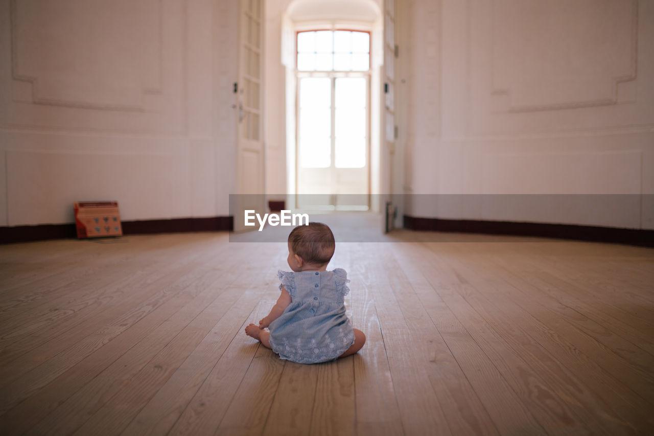 Rear View Of Girl Sitting On Hardwood Floor