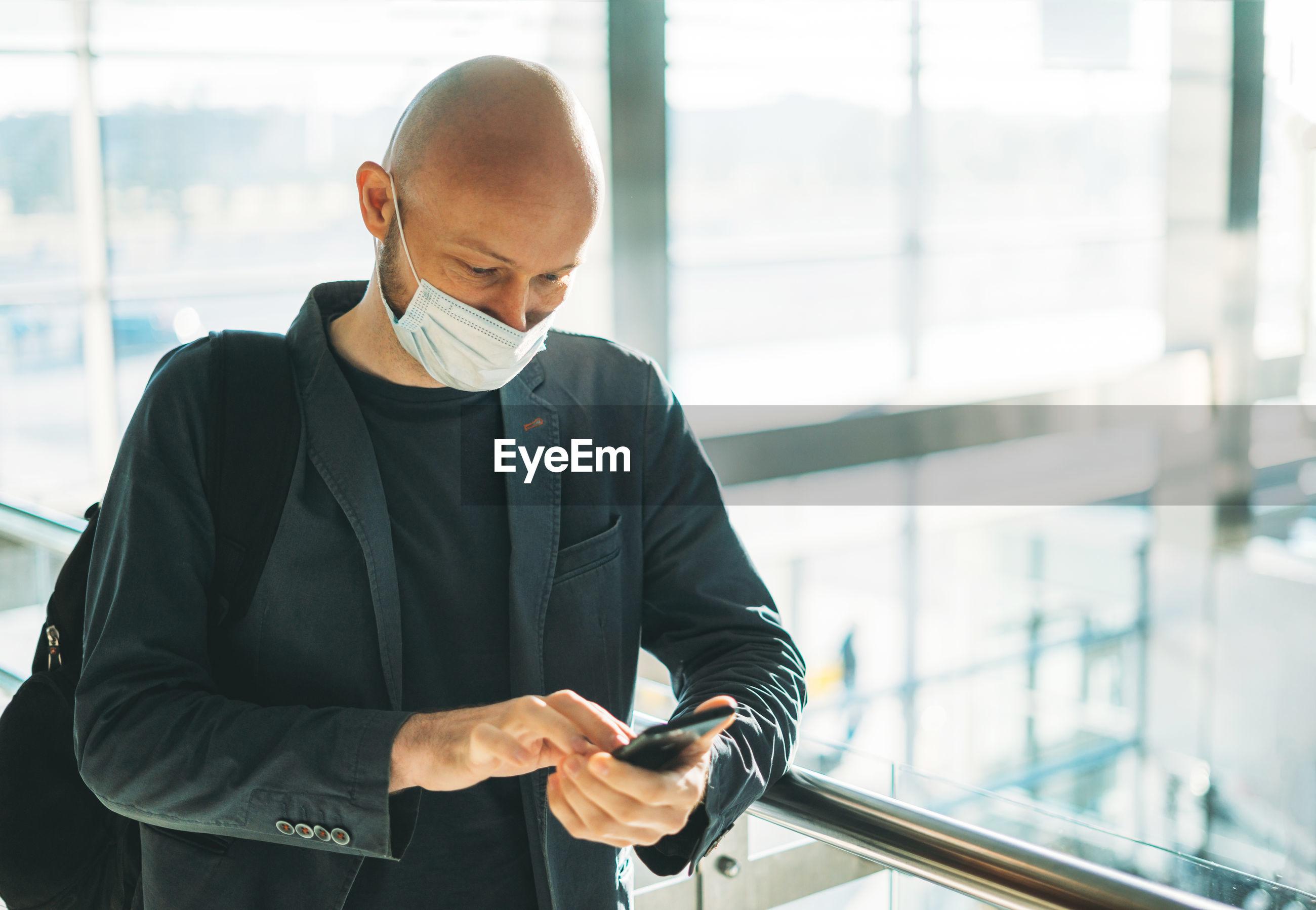 FULL LENGTH OF A MAN USING MOBILE PHONE