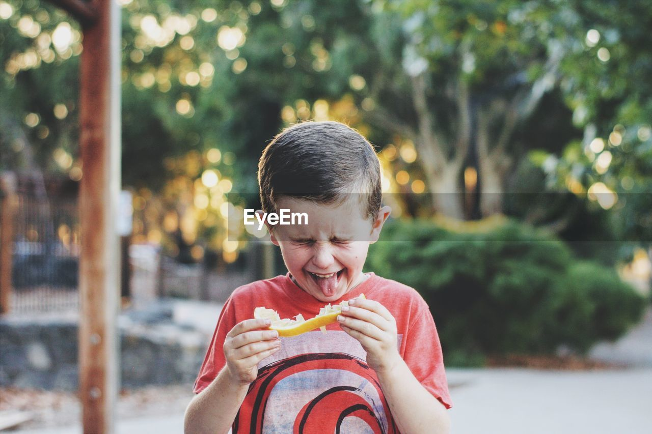 Cute boy sticking out tongue while holding food outdoors
